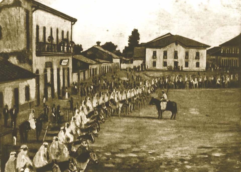 Grupo dos Zuavos, no carnaval de 1870, vendo-se, ao fundo, a Cadeia Velha, demolida erigindo no local o Monumento-túmulo de Carlos Gomes.  Extraído do livro